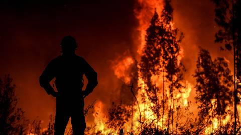 A firefighter monitors the progression of a wildfire at Amendoa in Macao, central Portugal on July 21, 2019. - More than a thousand firefighters battled to control wildfires in central Portugal that have forced village evacuations, in a region where dozens were killed in huge blazes in 2017. The firefighters were deployed to tackle three fires in the mountainous and heavily forested Castelo Branco region, 200 kilometres north of Lisbon, according to the website of the Civil Protection. (Photo by PATRICIA DE MELO MOREIRA / AFP)