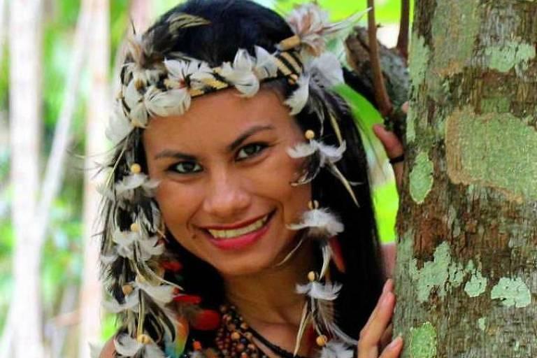 mulher de cabelo preto com algumas penas nos cabelos