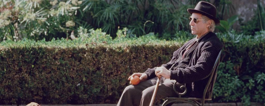 O envelhecido Michael Corleone está sentado em um jardim, com uma bengala e uma laranja nas mãos