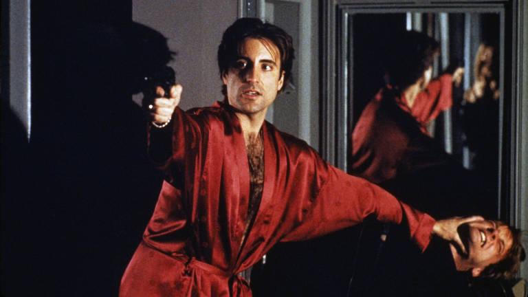 Homem com roupão vermelho segura outro com uma das mãos e aponta a arma para um terceiro, que não aparece no quadro
