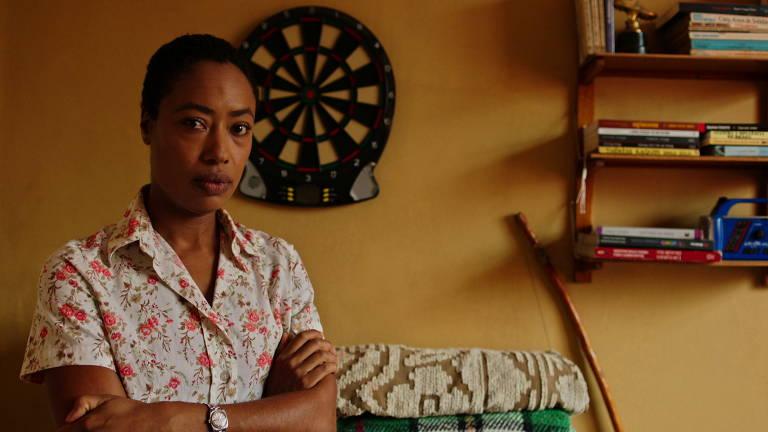 mulher negra de braços cruzados em quarto