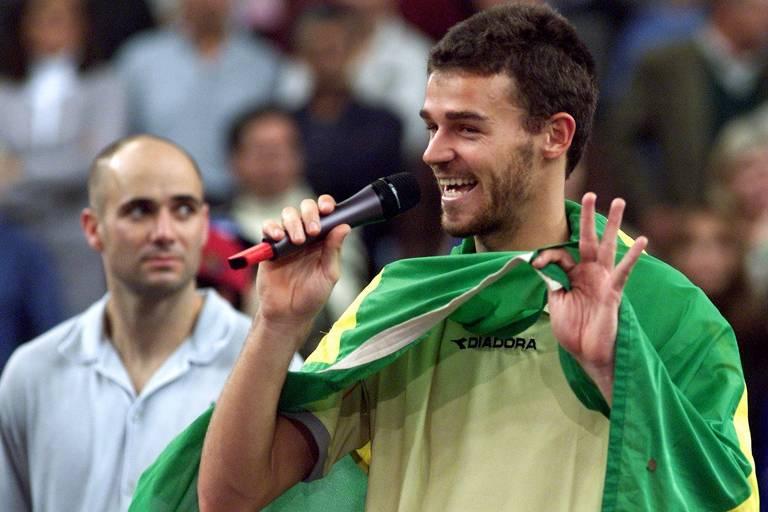 Gustavo Kuerten, com a bandeira brasileira amarrada às costas, faz o discurso da vitória ao lado de Andre Agassi, que ele derrotou na final da Masters Cup de Lisboa, em 2000