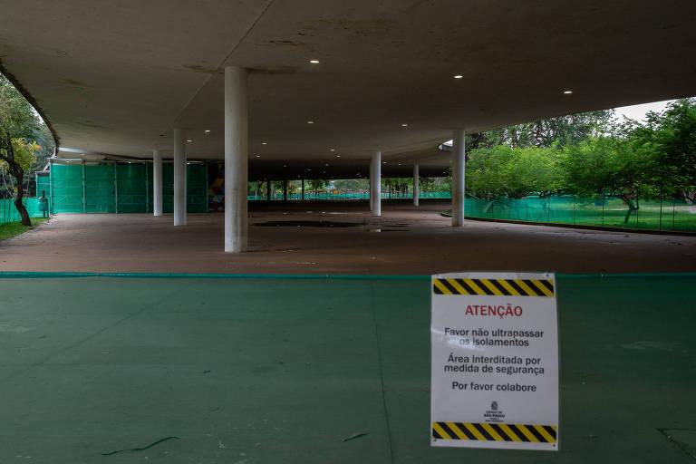 Marquise do parque Ibirapuera, após a interdição total determinada em liminar; mostra a estrutura cercada de telas verdes, com aviso de que é preciso respeitar a barreira por segurança