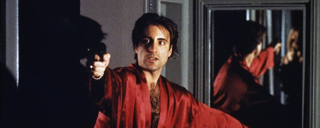 Homem com roupão vermelho aponta arma para alguém