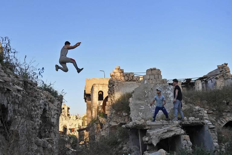 O parkour é um esporte que foi criado na França na década de 1990 e consiste em escalar e saltar ambientes da paisagem urbana, como prédios, escadas, corrimões e muros. Na foto, praticantes da modalidade saltam entre escombros em Aleppo, na Síria