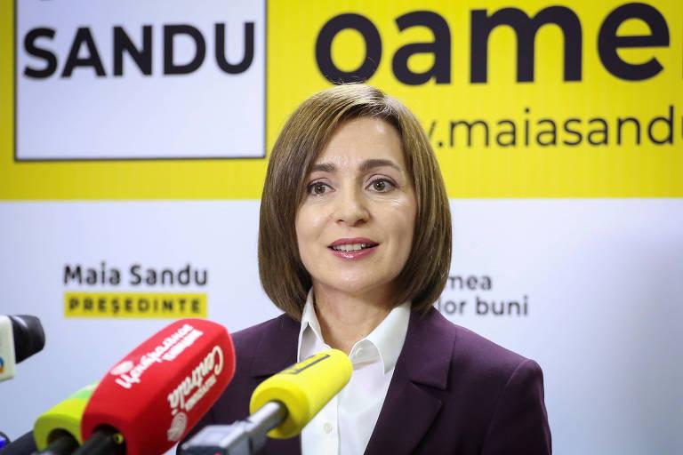 Mulher de cabelo curto, Maia Sandu, a presidente eleita da Moldova, com microfones à sua frente e um cartaz de propaganda política atrás