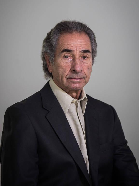 homem branco de cabelos grisalhos veste terno preto e posa para retrato