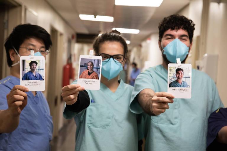 Três profissionais de saúde paramentados seguram crachás e sorriem por trás das máscaras