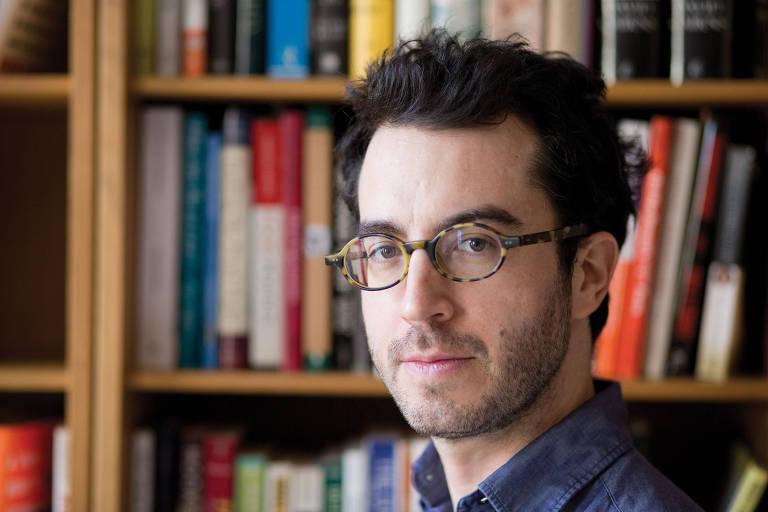 Homem branco ao lado de estante com livros