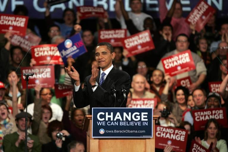 Barack Obama discursa, com apoiadores segurando cartazes ao fundo