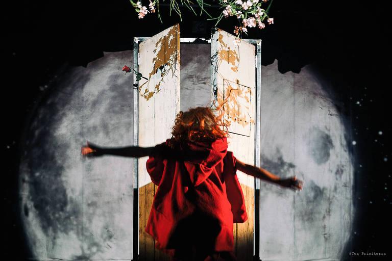 De costas, Chapeuzinho Vermelho entra numa porta, com a Lua ao fundo