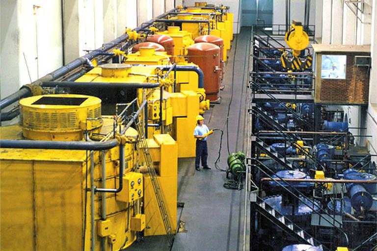 Galpão com máquinas amarelas e funcionários