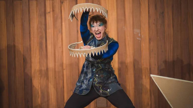 Atriz maquiada segura dentes de tubarão à sua frente