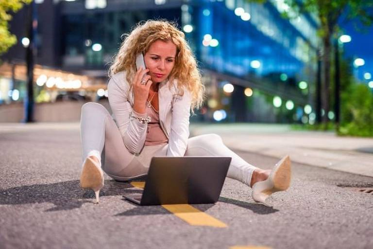Mulher com roupas sociais sentada no meio da rua falando no celular e mexendo no notebook