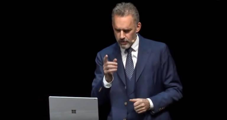 Homem branco de cabelo grisalho olha computador