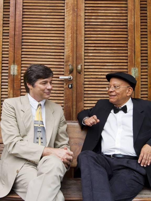 Dois homens de roupa formal lado a lado. Um é branco e outro negro
