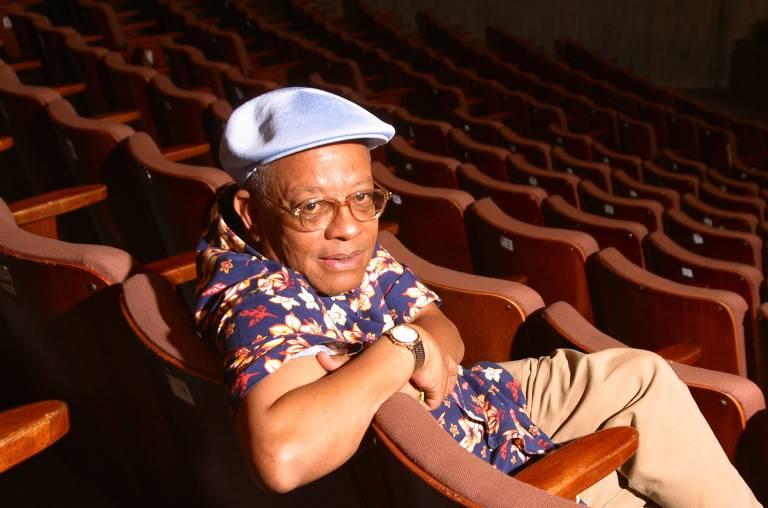 Homem negro com boina em auditório de cadeiras vermelhas