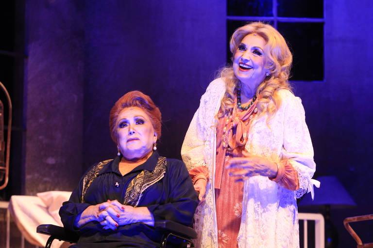 duas mulheres, uma sentada de mau humor e uma de pé sorrindo