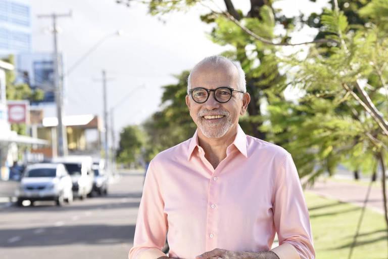 Edivaldo, um homem mais velho e de óculos e vestindo camisa, olhando para a câmera com uma rua ao fundo