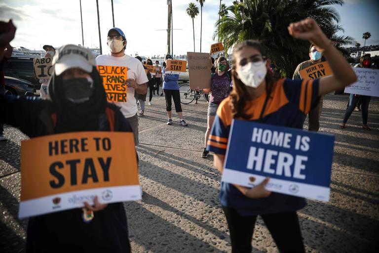 Manifestantes com cartazes que dizem 'aqui para ficar' e 'lar é aqui', durante protesto a favor do Daca em San Diego, na Califórnia