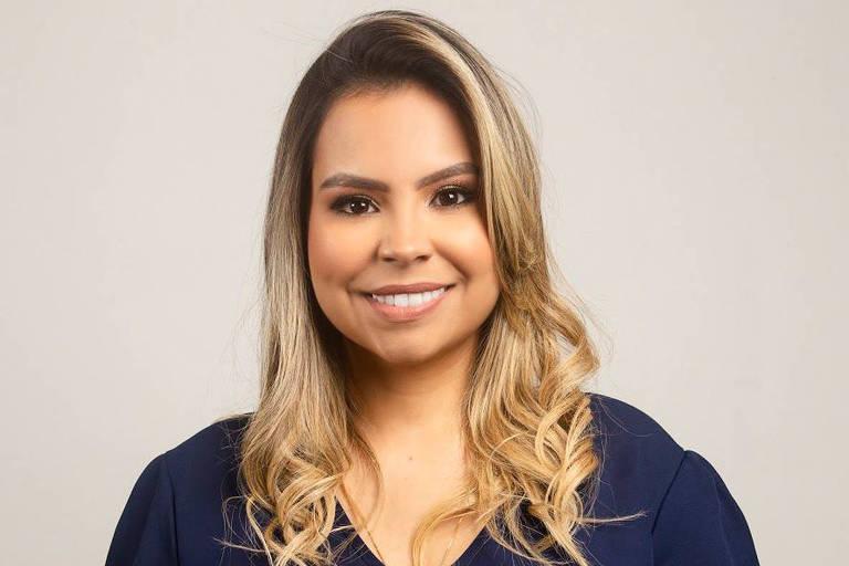 Uma mulher com cabelos loiros sorrindo para a foto
