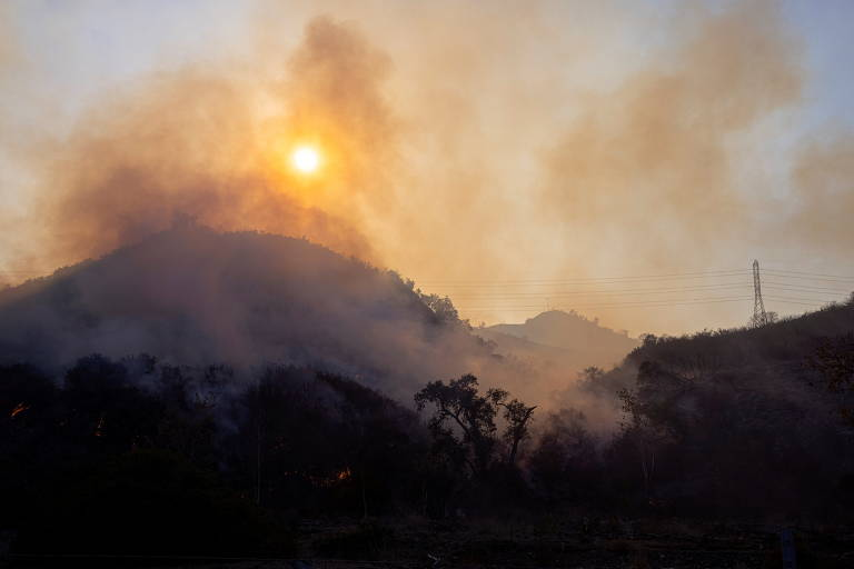 imagem mostra paisagem de montanhas, sombreada por fumaça proveniente de incêndio florestal