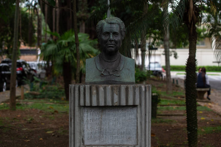 busto de mulher sobre pedestal com árvores ao fundo