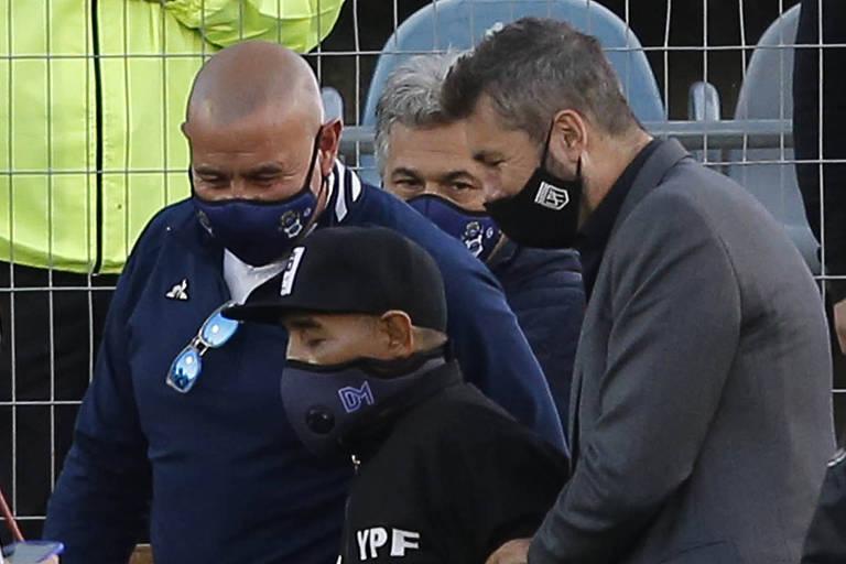 Maradona, amparado por Marcelo Tinelli (à dir.) e segurança do Gimnasia, deixa o campo após homenagem em 30 de outubro, dia do seu aniversário