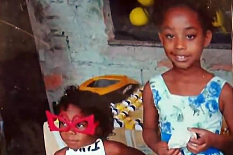 Emily Victória, 4, e sua prima Rebeca Beatriz, 7, foram baleadas na comunidade do Barro Vermelho, em Duque de Caxias; Emily está à esquerda, usa óculos de brinquedo vermelhos, gigantes para seu rosto, e olha para fora do quadro; do lado direito, Rebeca olha para a câmera, de vestido estampado de azul e branco; ao fundo uma parede sem reboco