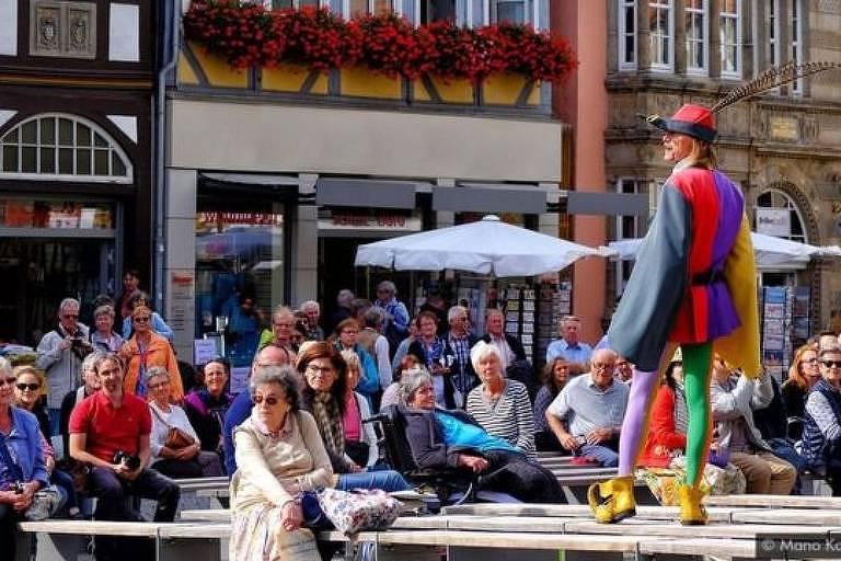 Homem está de pé diante de uma plateia em uma praça com prédios ao fundo. Ele veste meia-calça e roupas coloridas