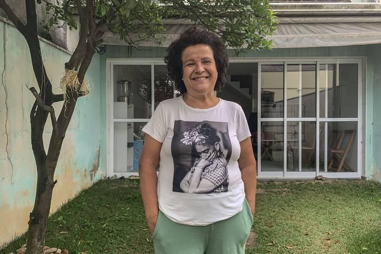 mulher de pé sorri para câmera, no quintal de sua casa, com mão no bolso, sobre a grama