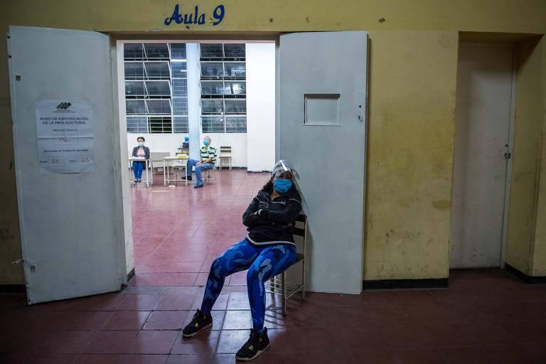 Mesários aguardam eleitores em centro de votação na capital neste domingo (6)