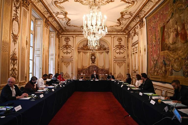 Em sala com paredes douradas, pé direito de mais ou menos quatro metros e lustre de cristal, pessoas se reúnem em mesa longa em forma de U