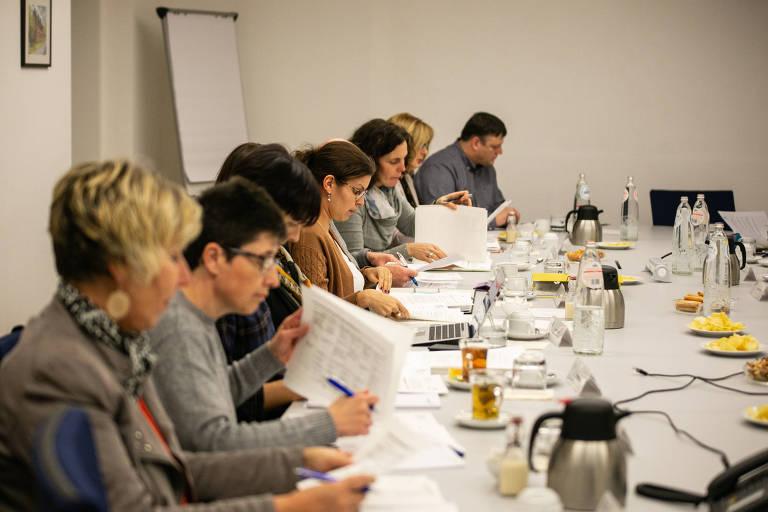 homens e mulheres de várias idades leem papeis e debatem em torno de mesa comprida