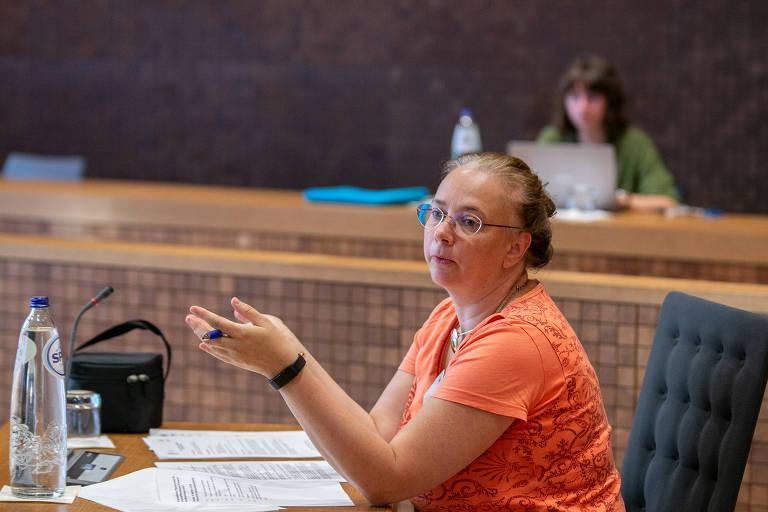Mulher de blusa laranja, óculos e cabelos presos em coque gesticula em mesa de plenário; ao fundo, moça olha para laptop