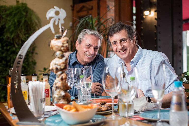 À frente de uma mesa cheia, os dois proprietários de restaurante sorriem para a câmera