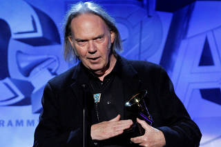 FILE PHOTO: Canadian singer songwriter Neil Young accepts his award at the 53rd annual Grammy Awards in Los Angeles