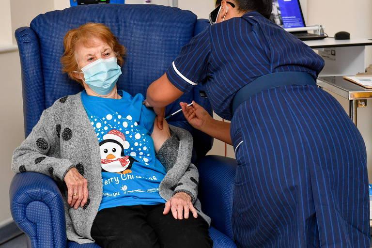 Enfermeira de uniforme azul escuro, de costas à direita da imagem, aplica injeção em senhora de camiseta azulcom desenho de um pinguim, casaco aberto cinza e máscara de proteção, cabelos ruivos curtos, sentada em poltrona azul marinho