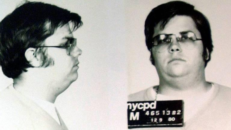 Homem branco gordo com óculos posa para foto de delegacia