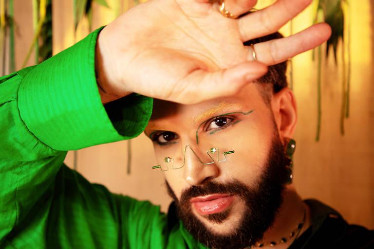 Imagem foca o rosto do cantor pernambucano Juan Guiã, que está maquiado, usa barba e está com a mão direita sobre a testa