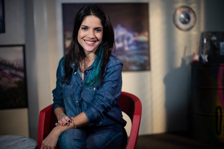 Roberta usa camisa jeans e sorri para a foto