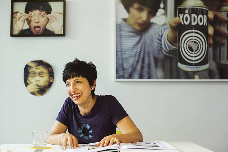 mulher branca, de cabelos pretos e curtos, está sentada à mesa em um ateliê com quadros pendurados. ela apoia os braços na mesa e sorri olhando para o lado