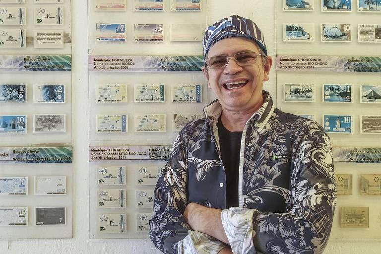 homem de roupas coloridas posa sorrindo e com as mãos cruzadas, com chapéu e óculos