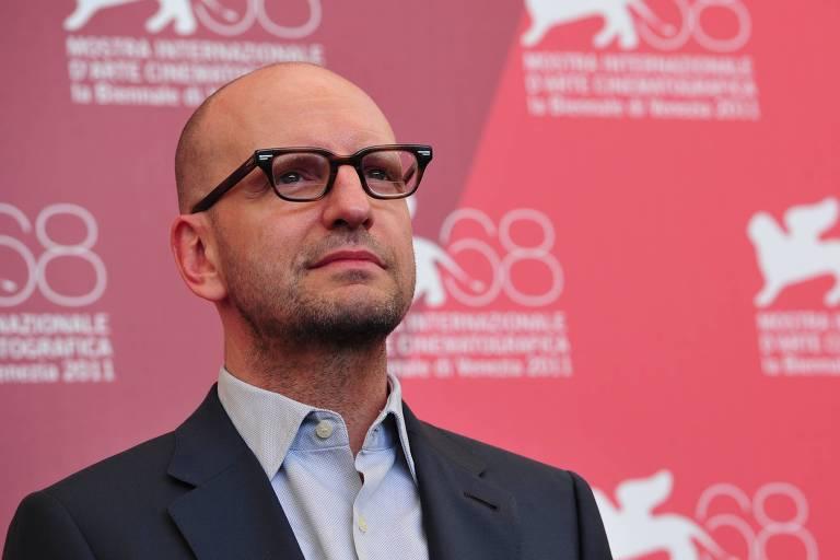 Homem branco careca de óculos usa terno em tapete vermelho