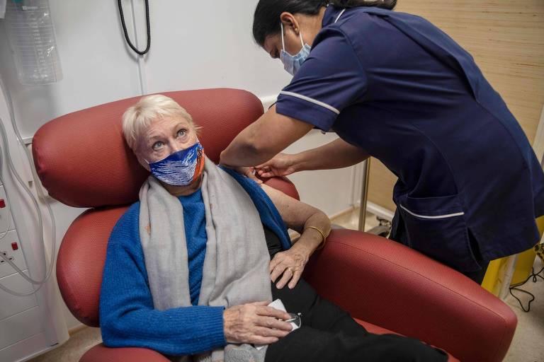 mulher idosa sentada recebe vacina; a enfermeira vestida de azul escuro aplica a vacina em pé