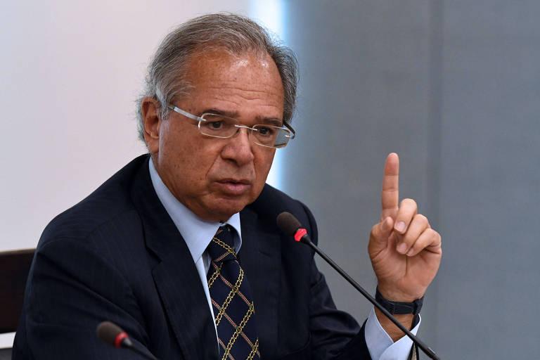 Paulo Guedes, de terno escuro, fala ao microfone e aponta com a mão esquerda para cima
