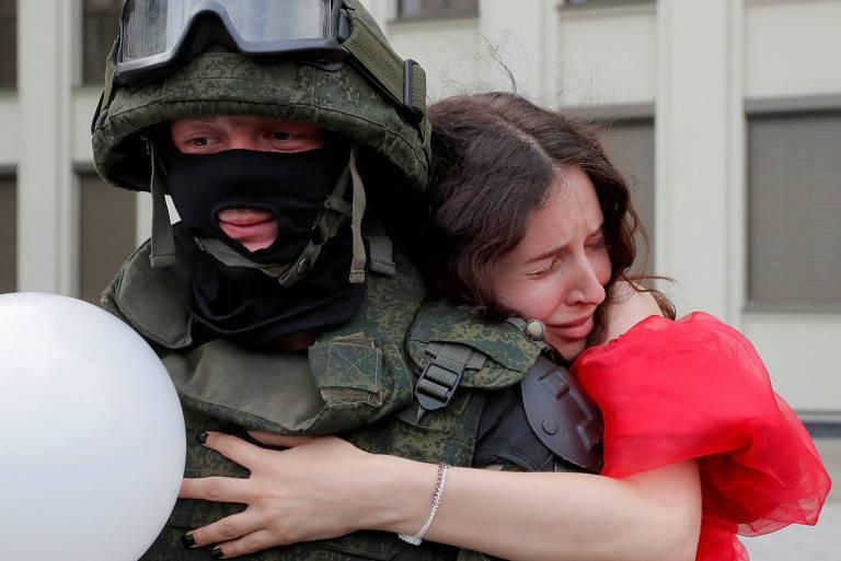 Manifestante pró-democracia abraça agente de segurança durante protesto contra o ditador de Belarus, Aleksandr Lukachenko
