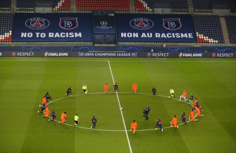 """Jogadores das duas equipes se ajoelham no centro do gramado, com os punhos erguidos. Ao fundo, as faixas com escudos de PSG e Istanbul e a frase """"Não ao racismo"""""""