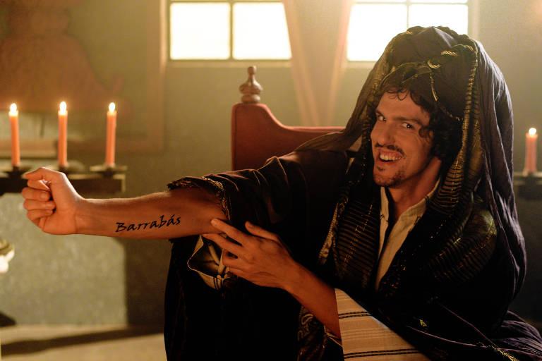 homem com roupa de epoca e tres velas ao fundo mostra braço com tatuagem escrito barrabás