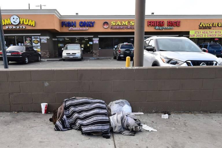 Morador de rua dorme em calçada diante de comércio aberto apesar das restrições para frear o coronavírus em Los Angeles, na Califórnia